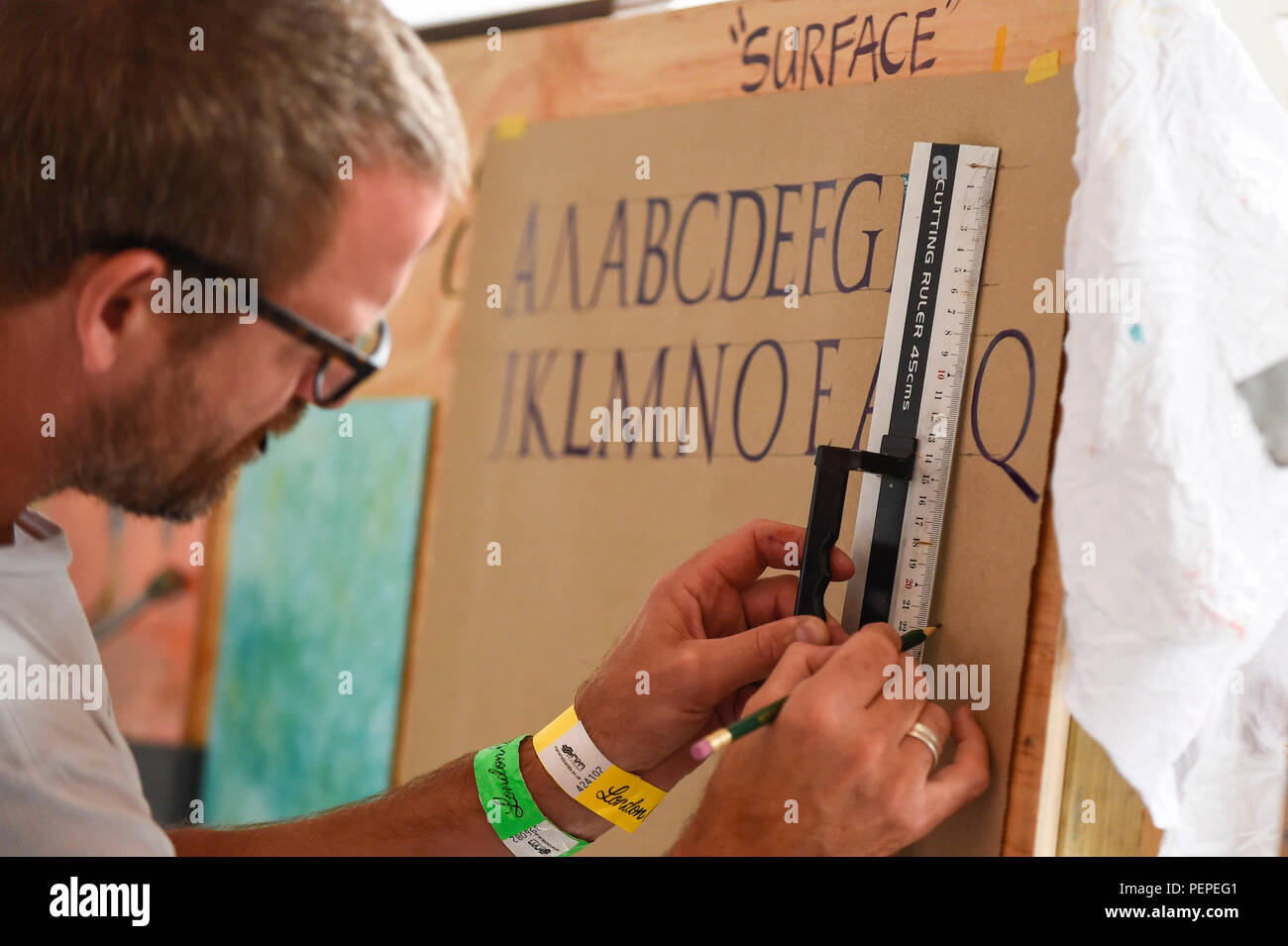 London, UK.  17 August 2018. A signwriter practices at 'Letterheads 2018:  London Calling', a gathering of international professional signwriters and lettering artists from over 30 countries.  Signwriters can network and learn new skills and visitors can see signwriting in action.  The event is taking place at the Bargehouse, Oxo Tower Wharf in central London until 19 August.  Credit: Stephen Chung / Alamy Live News - Stock Image