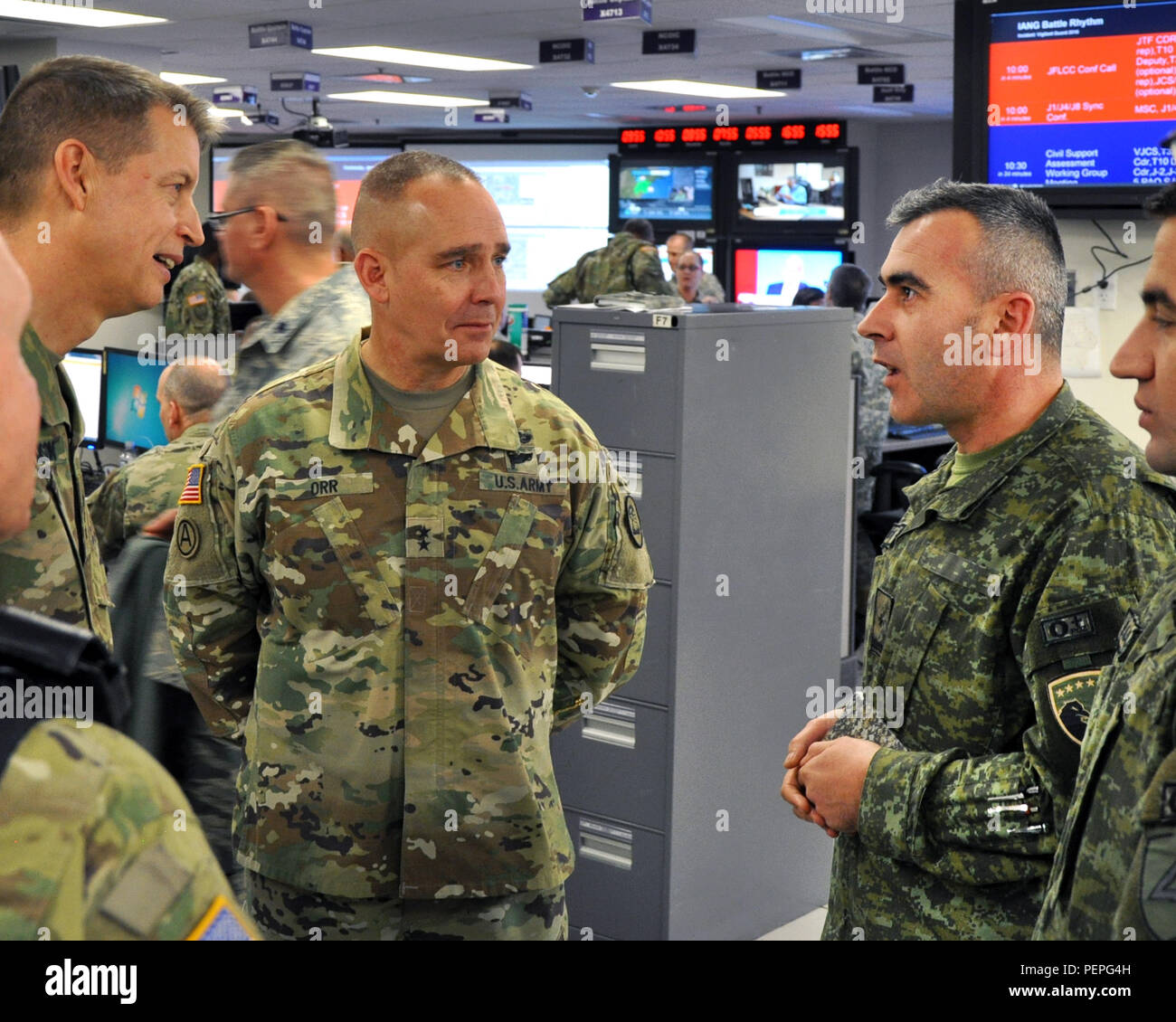 Lt. Gen. Daniel Hokanson (far left), deputy commander, U.S. Northern Command and Maj. Gen. Timothy Orr (center), the adjutant general of Iowa, speak with members of the Kosovo Security Forces in the Joint Operation Center at Joint Forces Headquarters, Johnston, Iowa, on Jan. 13, 2016, during the Vigilant Guard '16 exercise. (Iowa National Guard photo by Tech. Sgt. Michael B. McGhee) Stock Photo