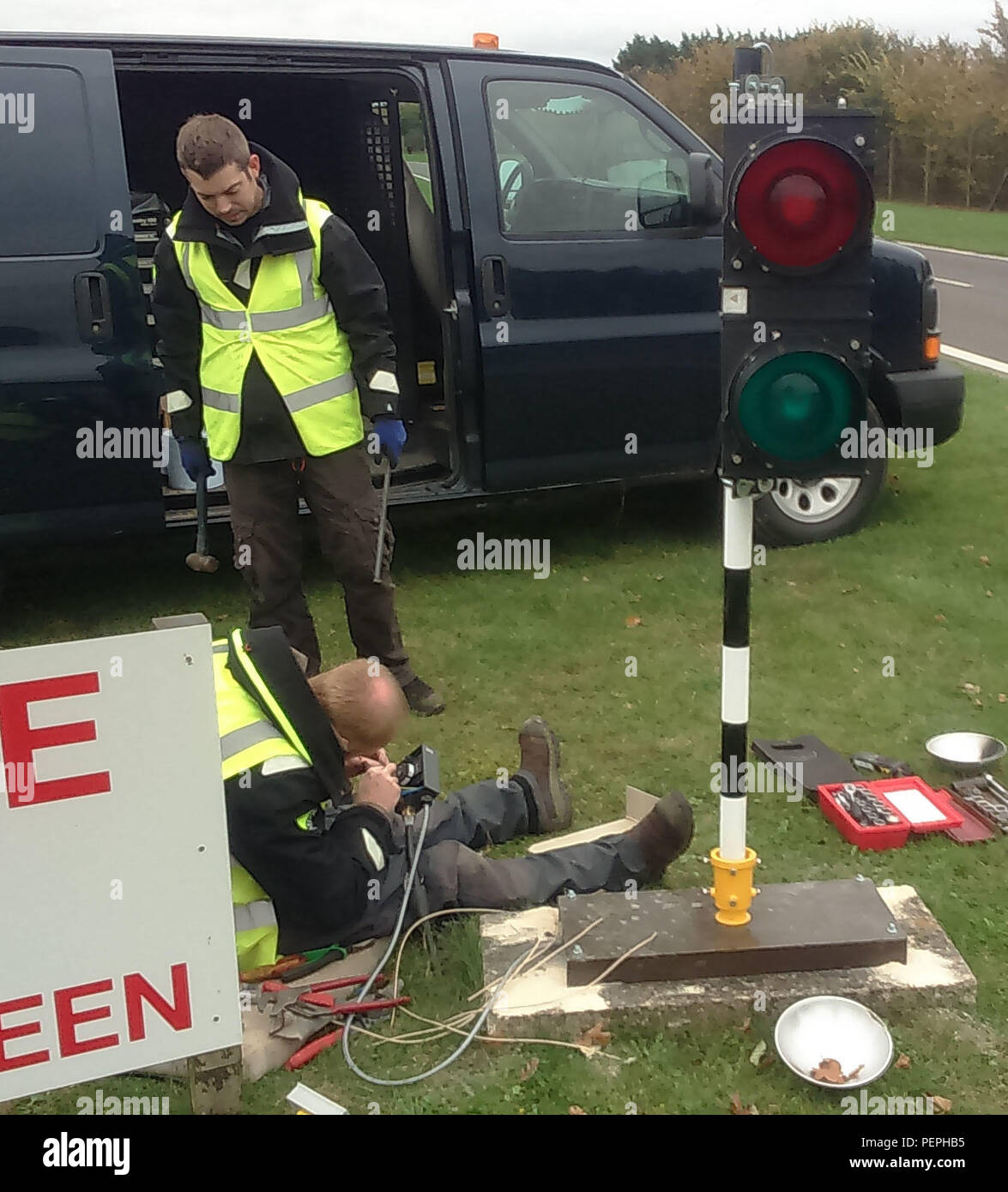 Members of the 100th Civil Engineer Squadron, connect the electrical control cables to the new perimeter road traffic lights Nov. 10, 2015, on RAF Mildenhall, England. These lights have been changed for safety reasons to stop vehicles entering the instrument landing system controlled areas. (Courtesy photo/Released) - Stock Image