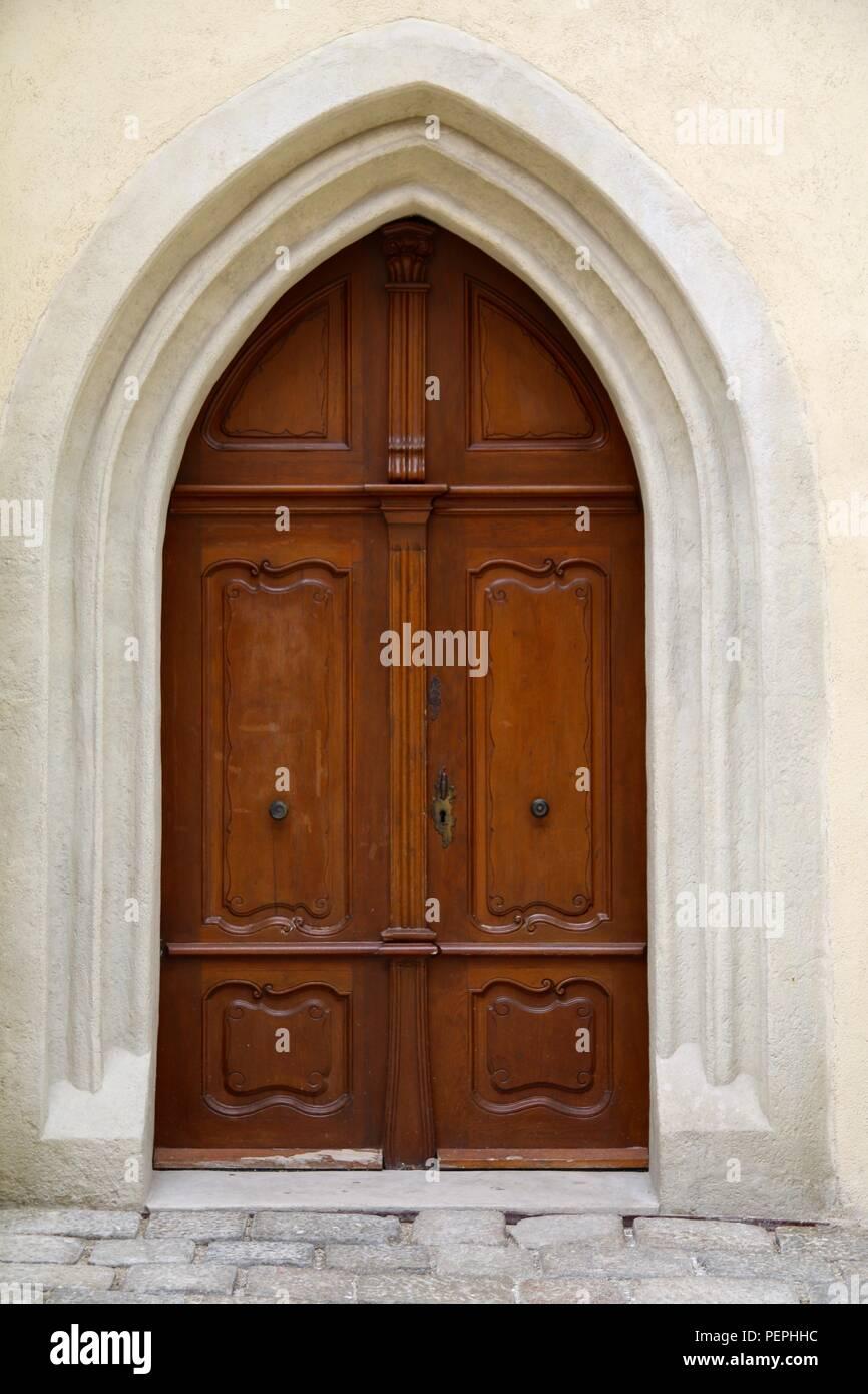 Double wooden doors in an arched doorway - Stock Image