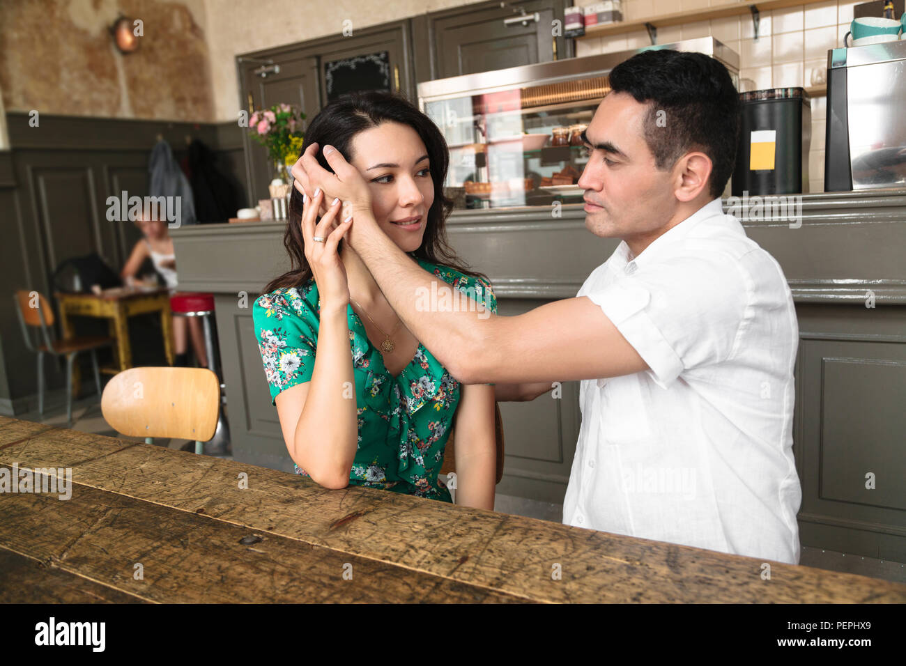 Man hugs his wife and gently touches her hair - Stock Image