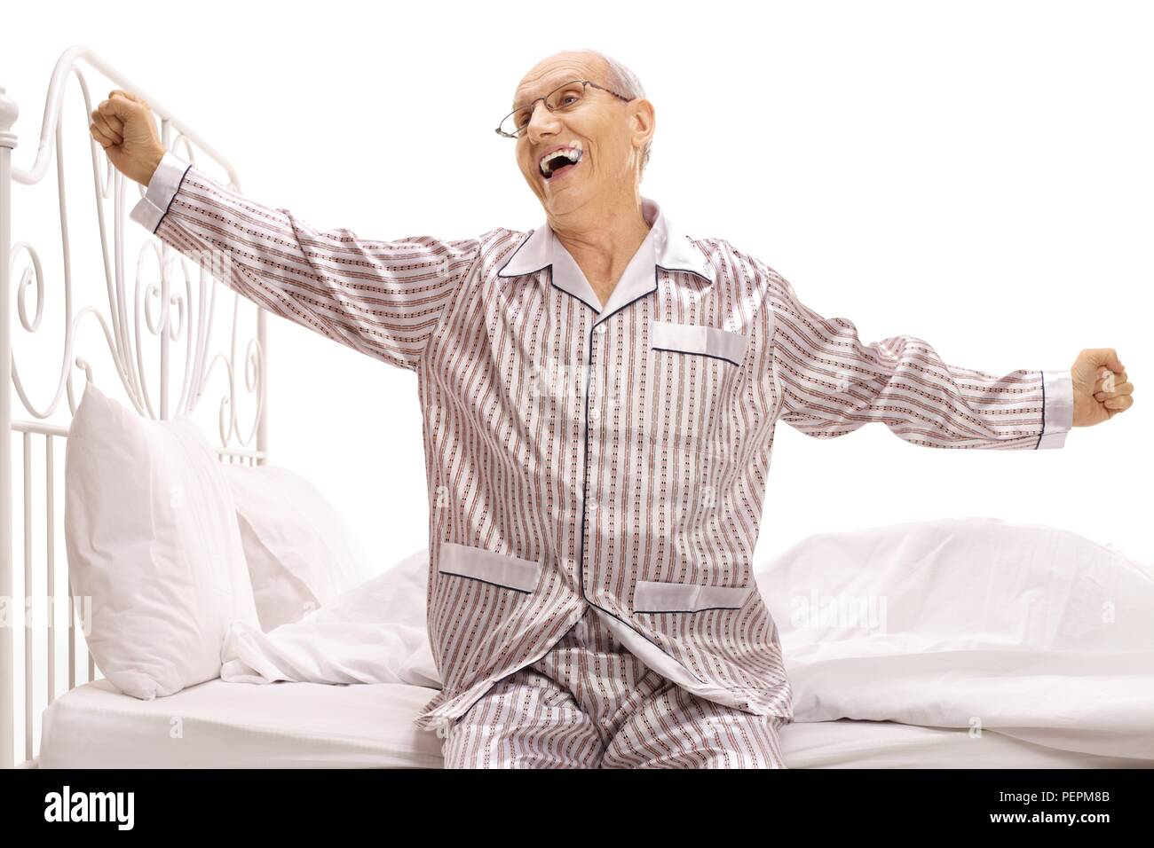 cd2104ccc2 Elderly man in pajamas sitting on a bed stretching himself isolated on white  background