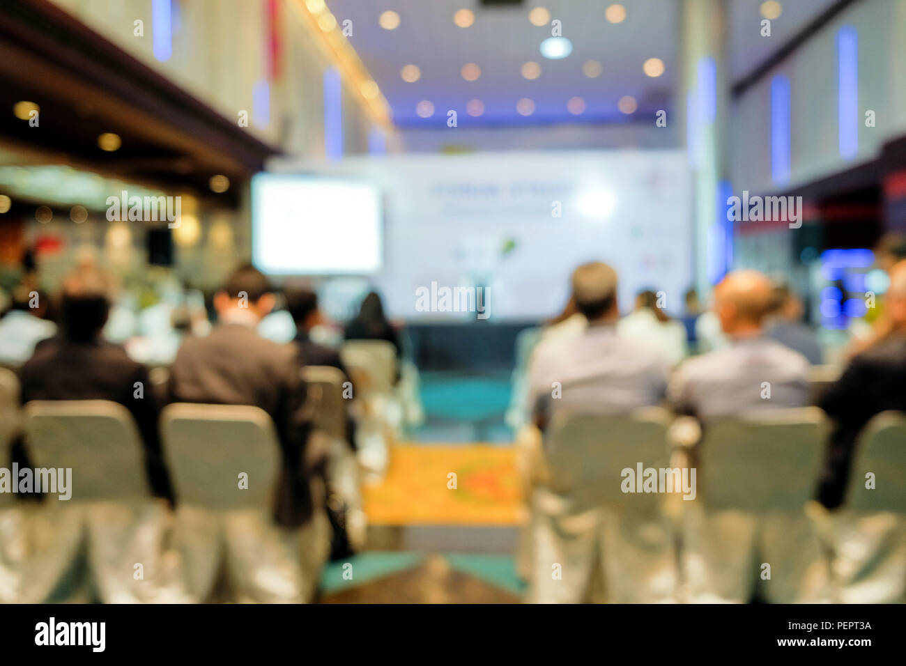 Blurred view from behind the audience waiting to hear from the speaker in the seminar in the building on blurred background. - Stock Image