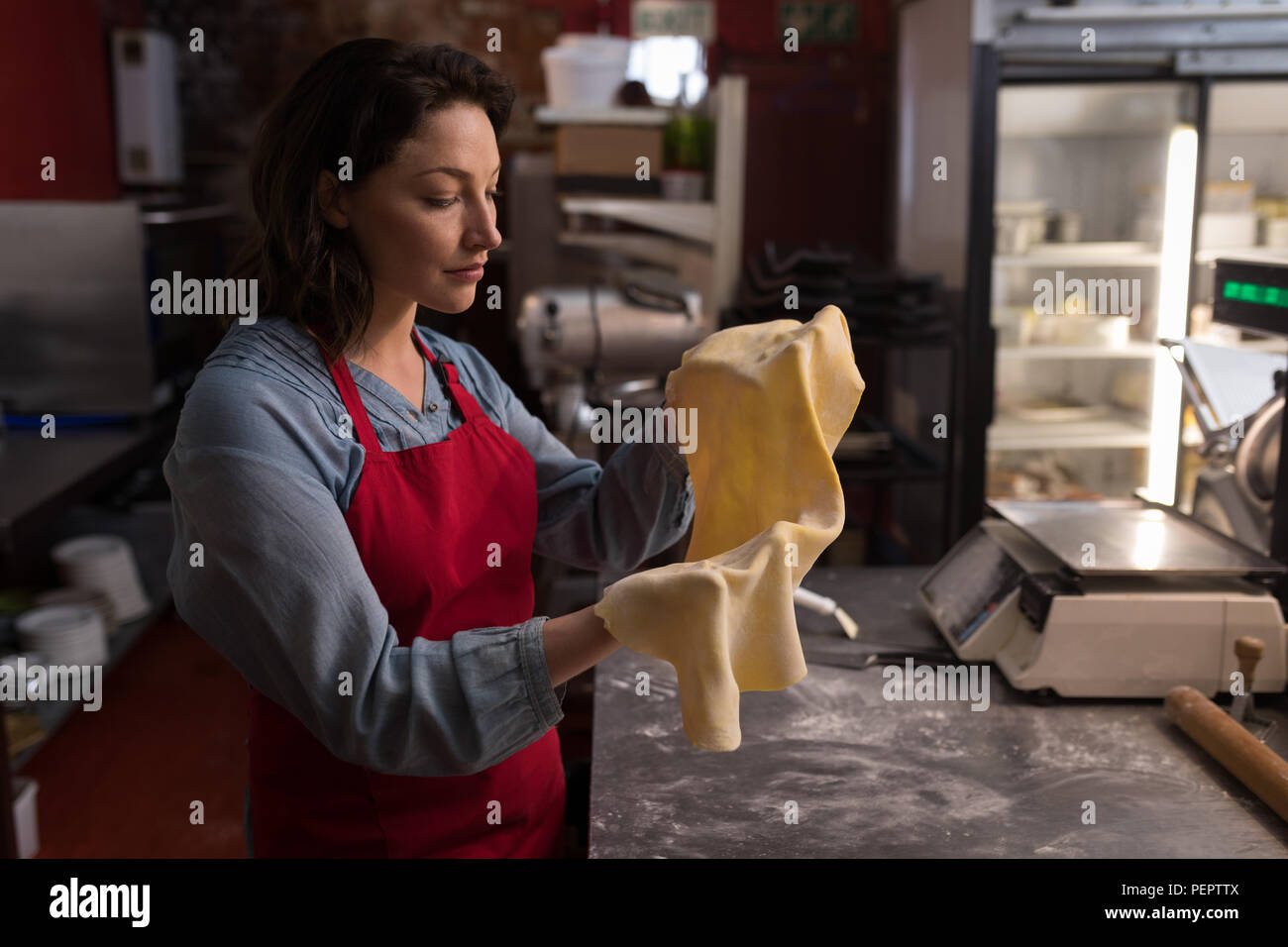 Female baker holding a pasta in hand - Stock Image