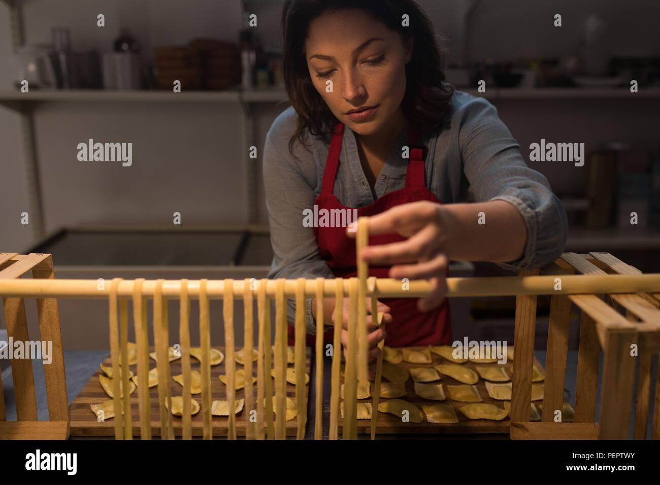 Female baker preparing pasta in bakery - Stock Image