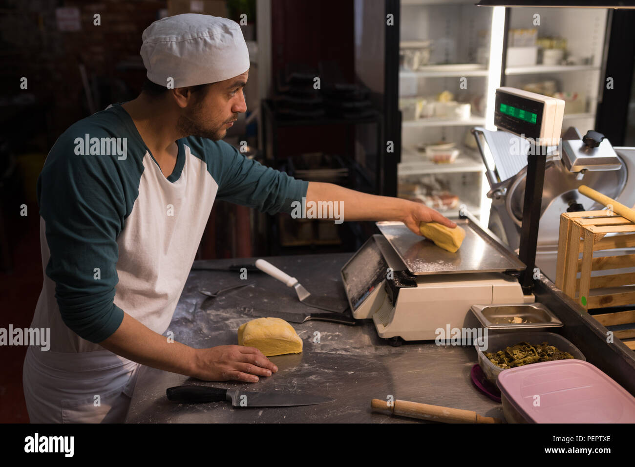 Male baker checking weight of dough - Stock Image