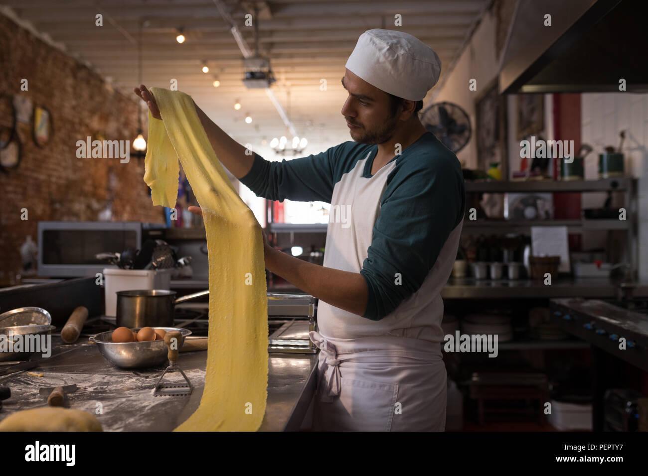Baker preparing pasta in bakery - Stock Image