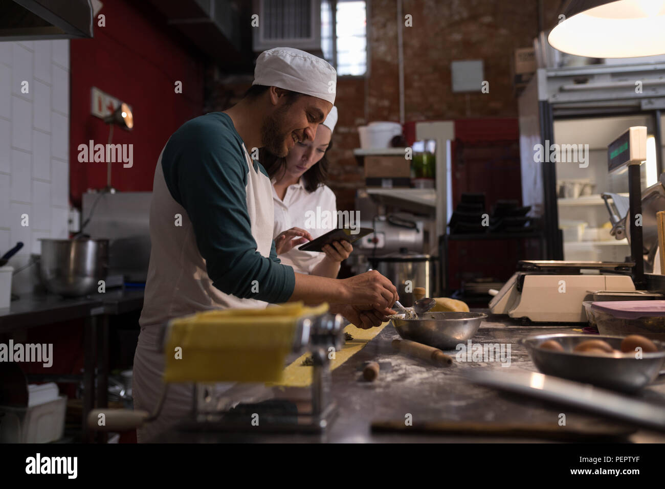 Baker preparing pasta while co-worker using digital tablet his beside - Stock Image