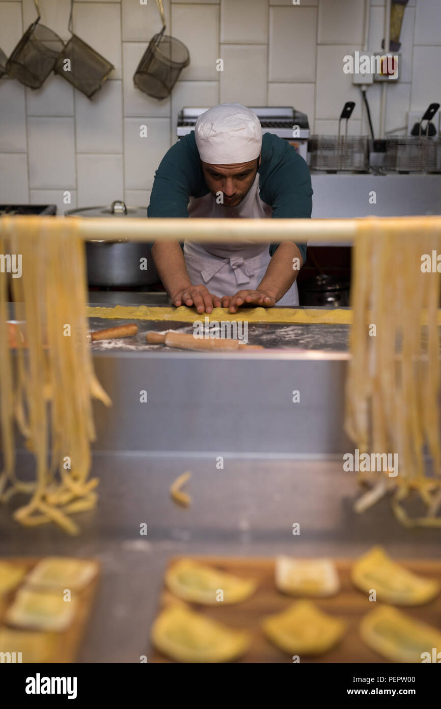 Male baker preparing pasta in bakery - Stock Image
