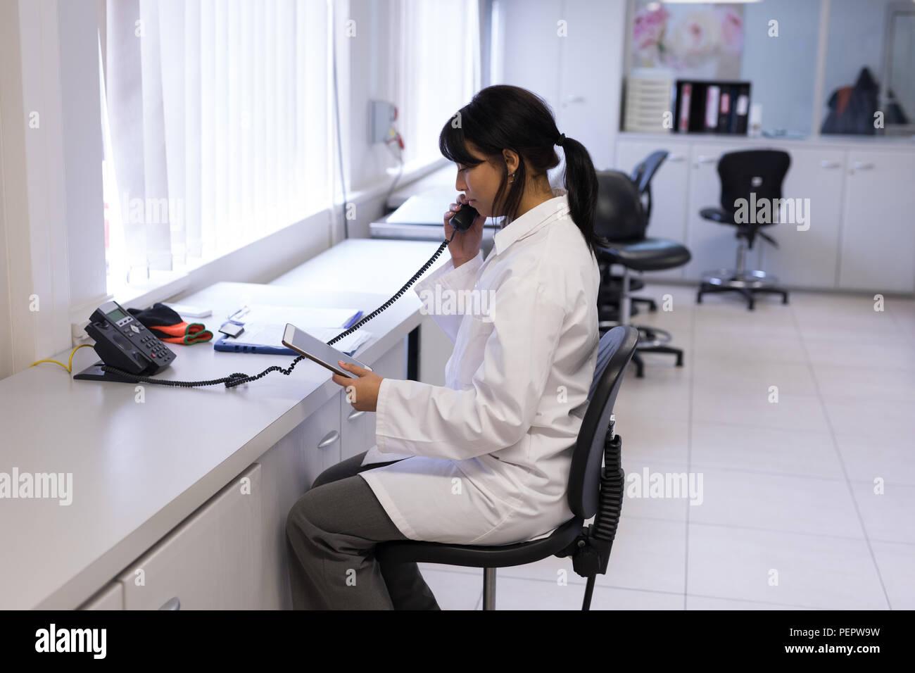 Laboratory technician talking on telephone - Stock Image