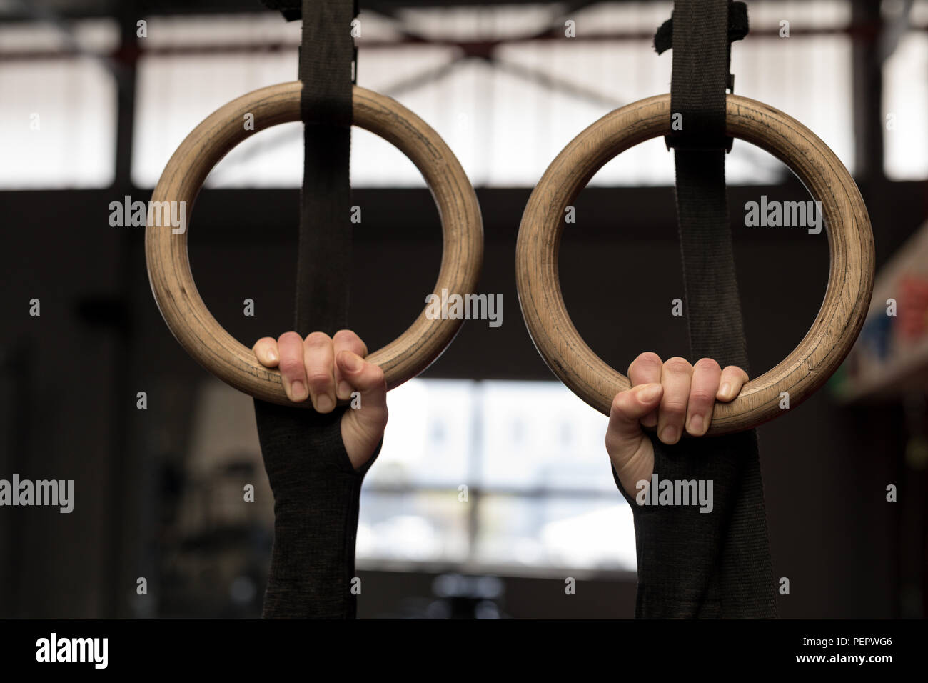 Woman exercising on gymnastic rings in fitness gym - Stock Image