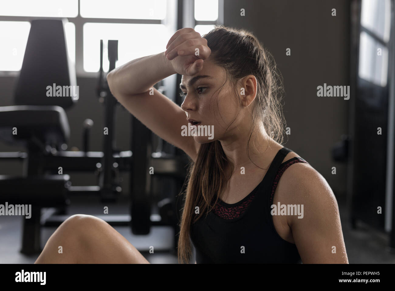Woman wipes sweat after workout in fitness studio - Stock Image