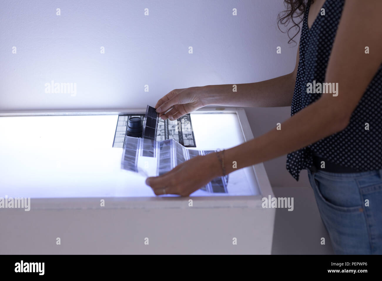 Female model looking at filmstrip in photo studio - Stock Image