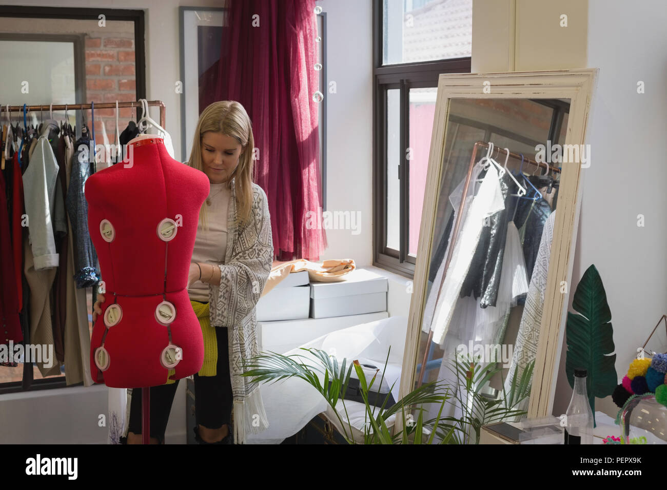 Fashion designer dressing mannequin - Stock Image