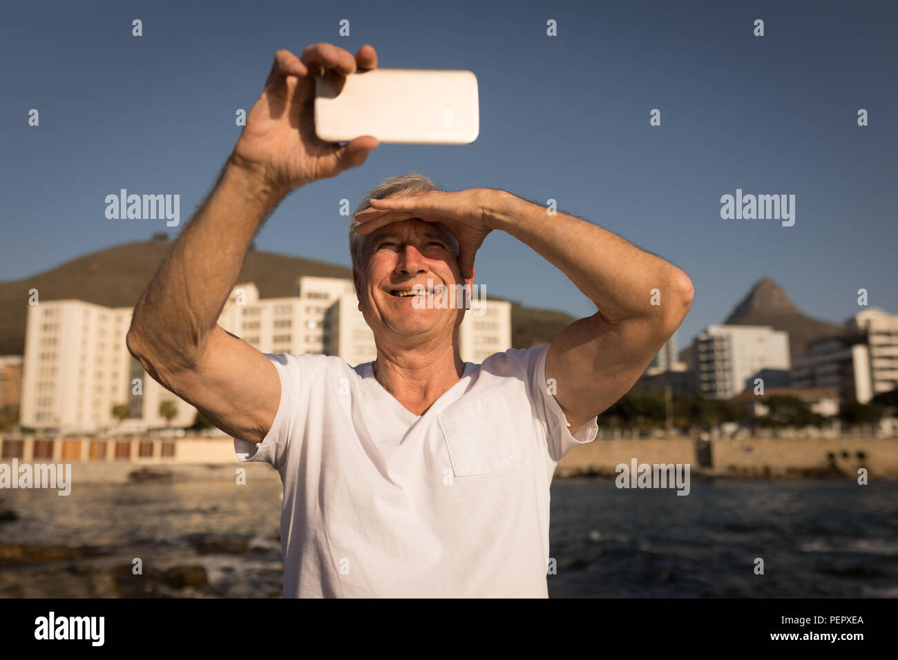 Senior man taking selfie near sea side - Stock Image