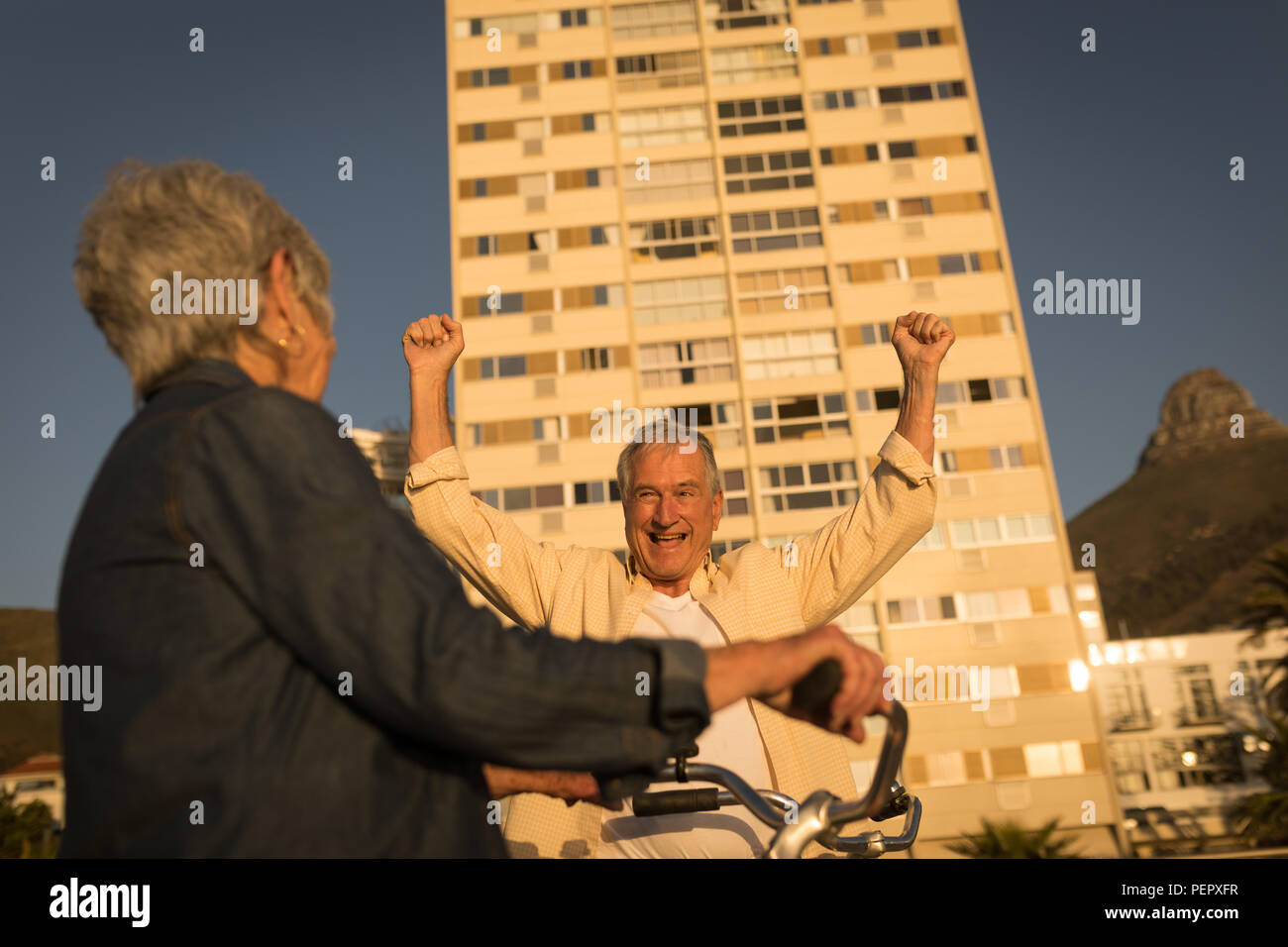 Senior man cheering at promenade - Stock Image
