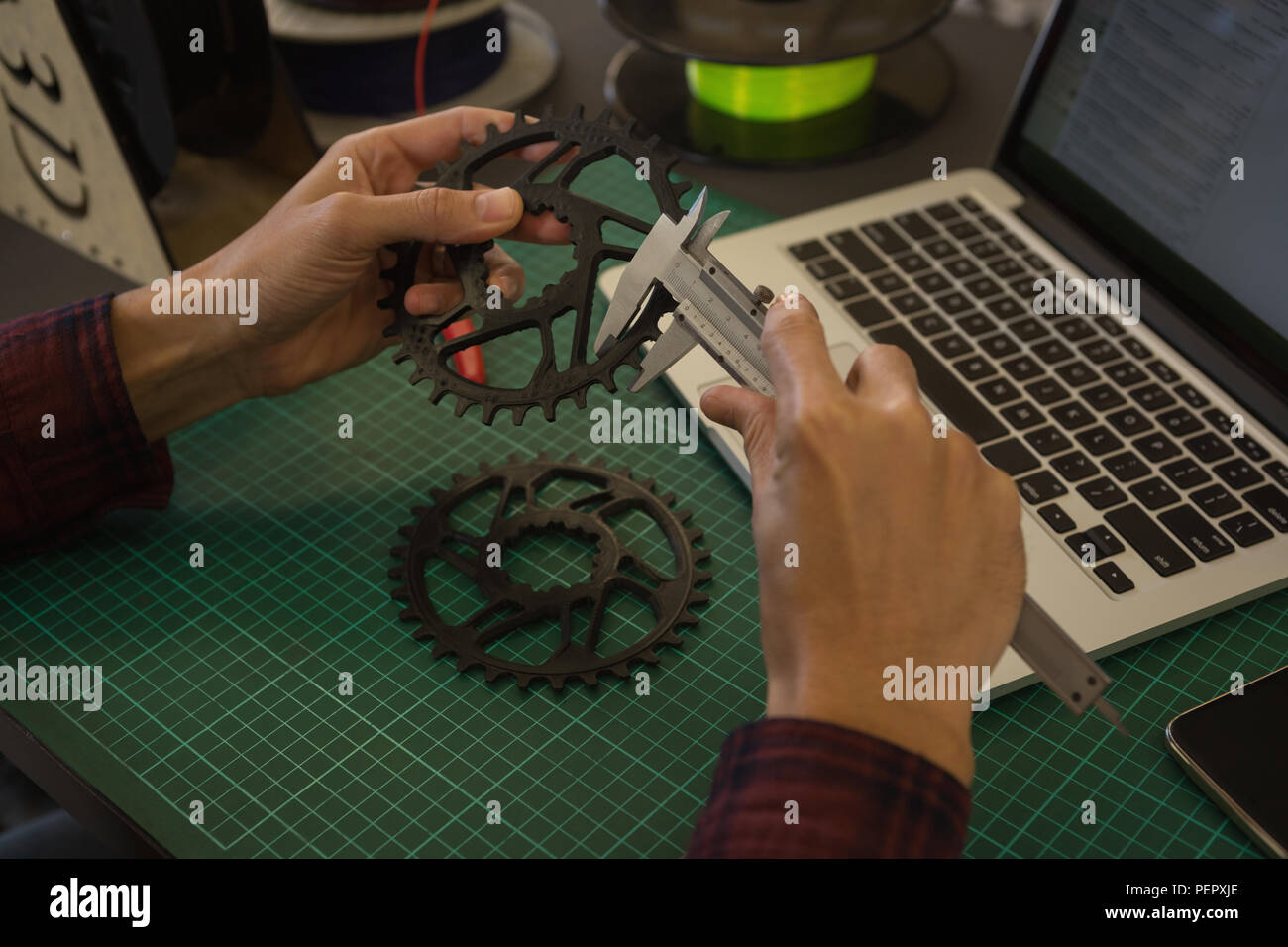 Mechanic checking diameter of chain ring with vernier calipers in workshop - Stock Image