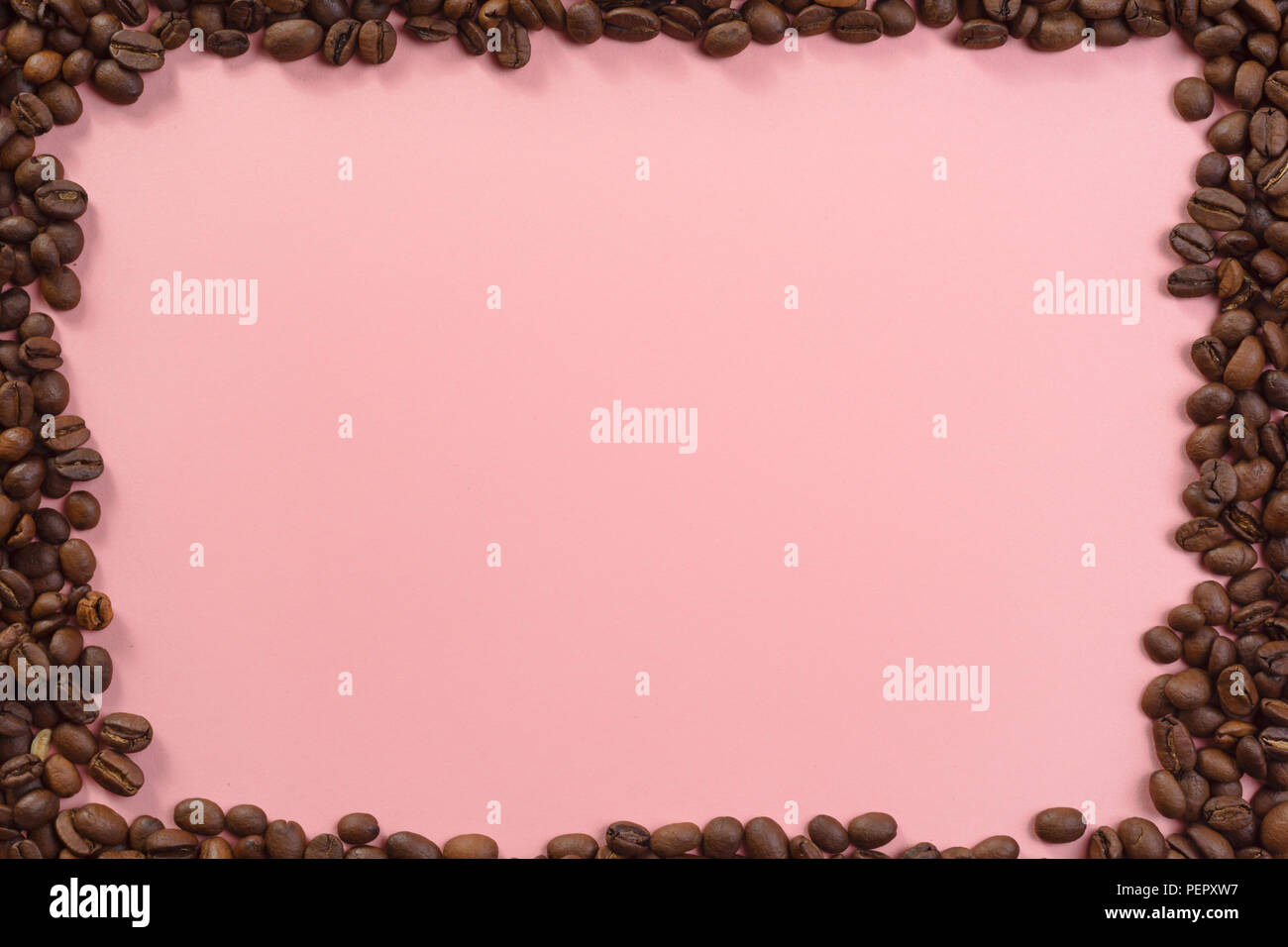 Lots of coffee beans around pastel background website textspace - Stock Image