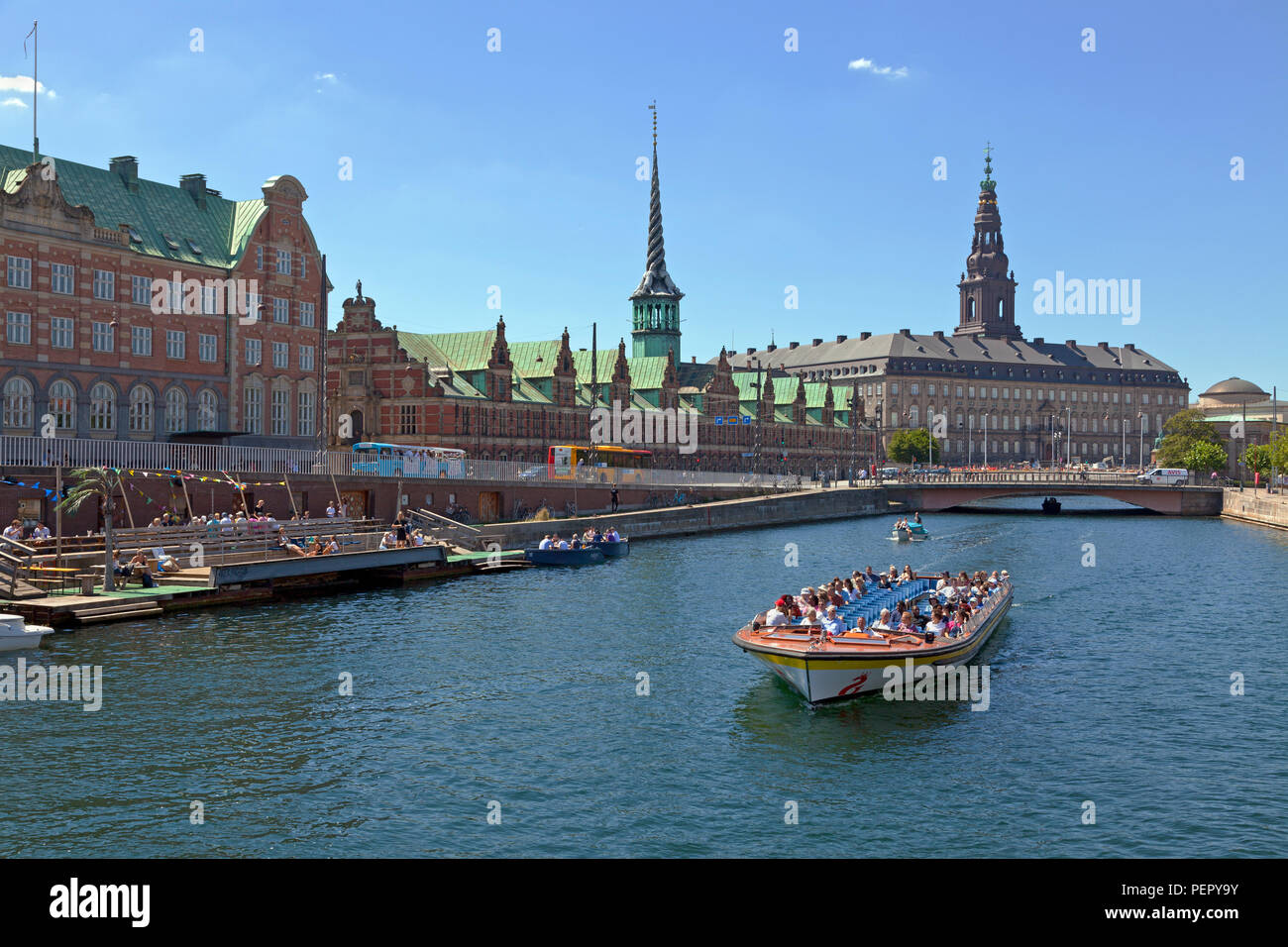 Canal cruise boat in Slotsholm Canal in Copenhagen. Christiansborg Castle, the Parliament,  the old stock exchange and dockside cafe and kayak rental.Stock Photo