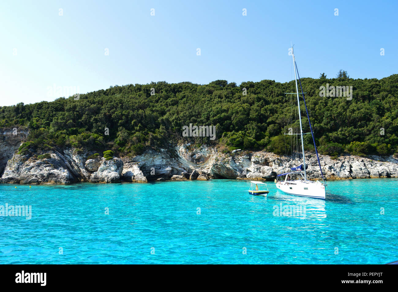Breathtaking blue sea at Antipaxos, Greece. Trees all around and two boats over the water. A totally summer shot ! - Stock Image