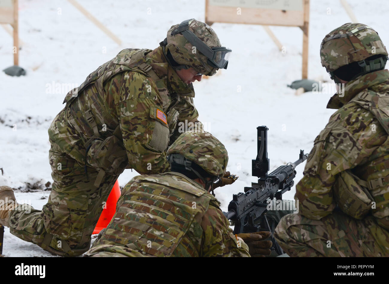Pfc. Collin Sapp (left), an assistant gunner with 3rd Squadron, 2nd Cavalry Regiment, stationed at Vilseck, Germany, originally from Muldrow, Okla., prepares to feed an M240 machine gun during a training exercise at Adazi Training Area in Latvia, Jan. 25, 2016. (U.S. Army photo by Staff Sgt. Steven Colvin/Released) - Stock Image
