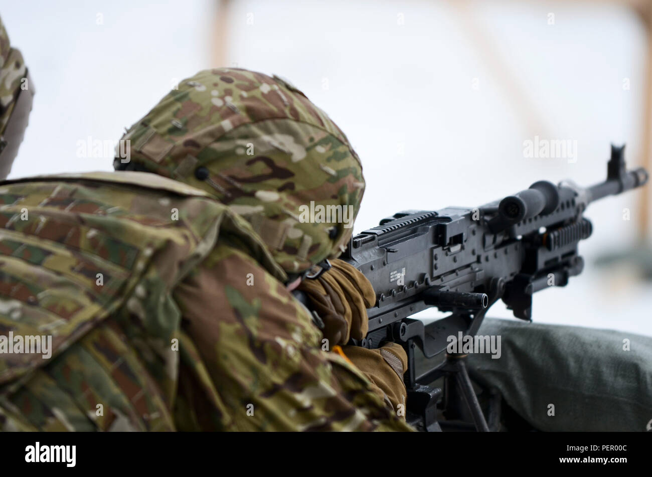 Pvt. Traverse Jarman, a scout with 3rd Squadron, 2nd Cavalry Regiment, stationed at Vilseck, Germany, originally from Crestwood, Ill., fires an M240 machine gun at a target during a training exercise at Adazi Training Area in Latvia, Jan. 25, 2016. (U.S. Army photo by Staff Sgt. Steven Colvin/Released) - Stock Image