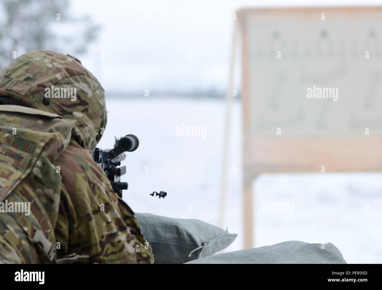 A clip is ejected from an M240 machine gun as a Soldier of 3rd Squadron, 2nd Cavalry Regiment, stationed at Vilseck, Germany, fires the weapon during a training exercise at Adazi Training Area in Latvia, Jan. 25, 2016. (U.S. Army photo by Staff Sgt. Steven Colvin/Released) - Stock Image