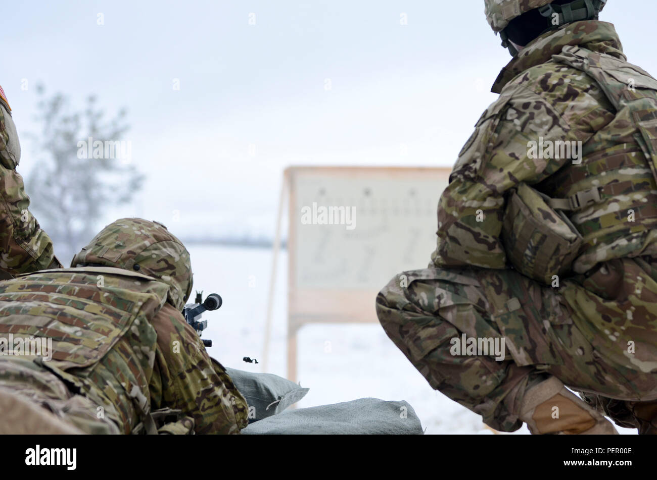 Staff Sgt. Andrew Nee (right), an engineer squad leader with 3rd Squadron, 2nd Cavalry Regiment, stationed at Vilseck, Germany, originally from Harlan, Iowa, coaches a Soldier at an M240 machine gun range during a training exercise at Adazi Training Area in Latvia, Jan. 25, 2016. (U.S. Army photo by Staff Sgt. Steven Colvin/Released) - Stock Image
