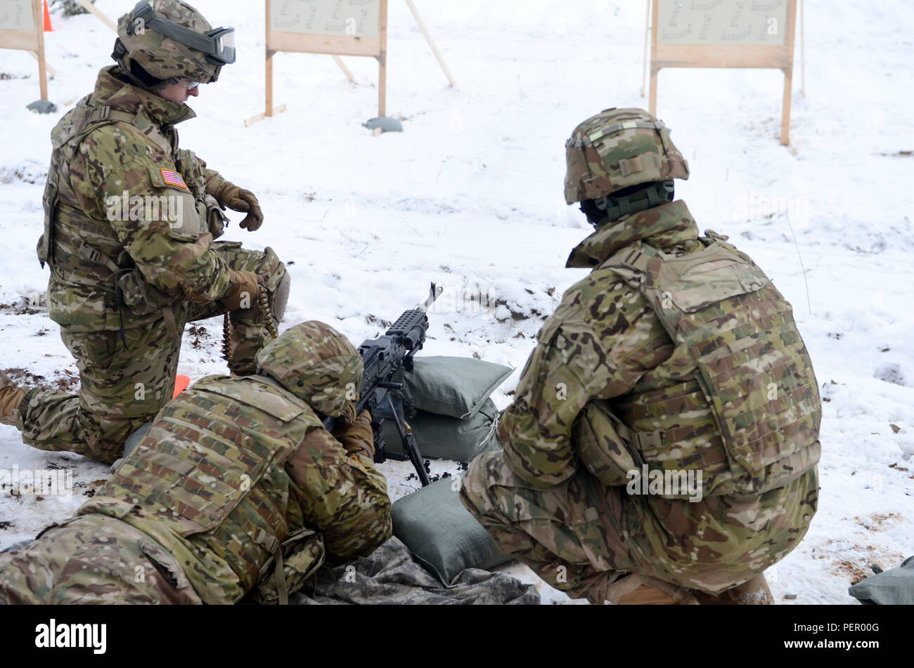 Pvt. Traverse Jarman (center), originally from Crestwook, Ill., fires an M240 machine gun as Pfc.Collin Sapp (left), originally from Muldrow, Okla., feeds the ammunition and Staff Sgt. Andrew Nee (right), originally from Harlan, Iowa, coaches during a training exercise at Adazi Training Area in Latvia, Jan. 25, 2016. All three Soldiers are with 3rd Squadron, 2nd Cavalry Regiment, stationed at Vilseck, Germany, in support of Atlantic Resolve. (U.S. Army photo by Staff Sgt. Steven Colvin/Released) - Stock Image