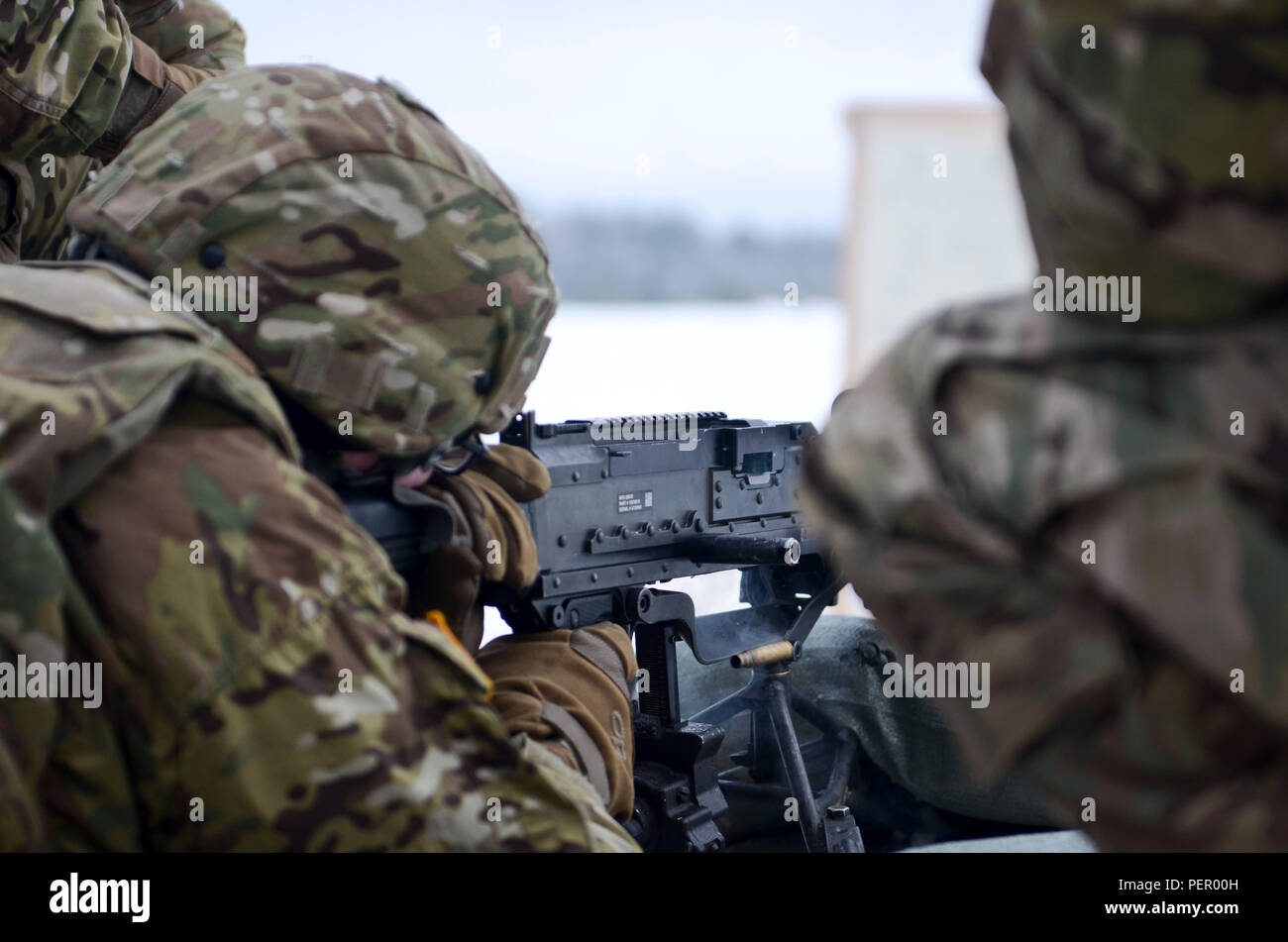 A round is ejected from an M240 machine gun as a Soldier of 3rd Squadron, 2nd Cavalry Regiment, stationed at Vilseck, Germany, fires the weapon during a training exercise at Adazi Training Area in Latvia, Jan. 25, 2016. (U.S. Army photo by Staff Sgt. Steven Colvin/Released) - Stock Image
