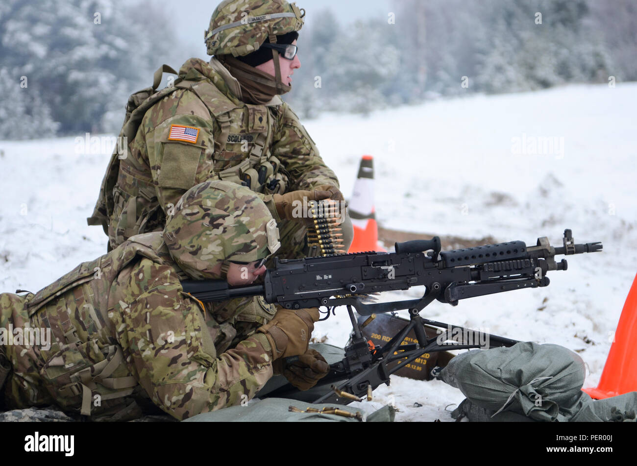 Pvt. Gage Adams, a scout and native from Springboro, Pa., fires an M240 machine gun as Spc. Michael Scollard, a radiotelephone operator, originally from Springfield, Va., both with 3rd Squadron, 2nd Cavalry Regiment, stationed at Vilseck, Germany, feeds the ammunition during a training exercise at Adazi Training Area in Latvia, Jan. 25, 2016. (U.S. Army photo by Staff Sgt. Steven Colvin/Released) - Stock Image