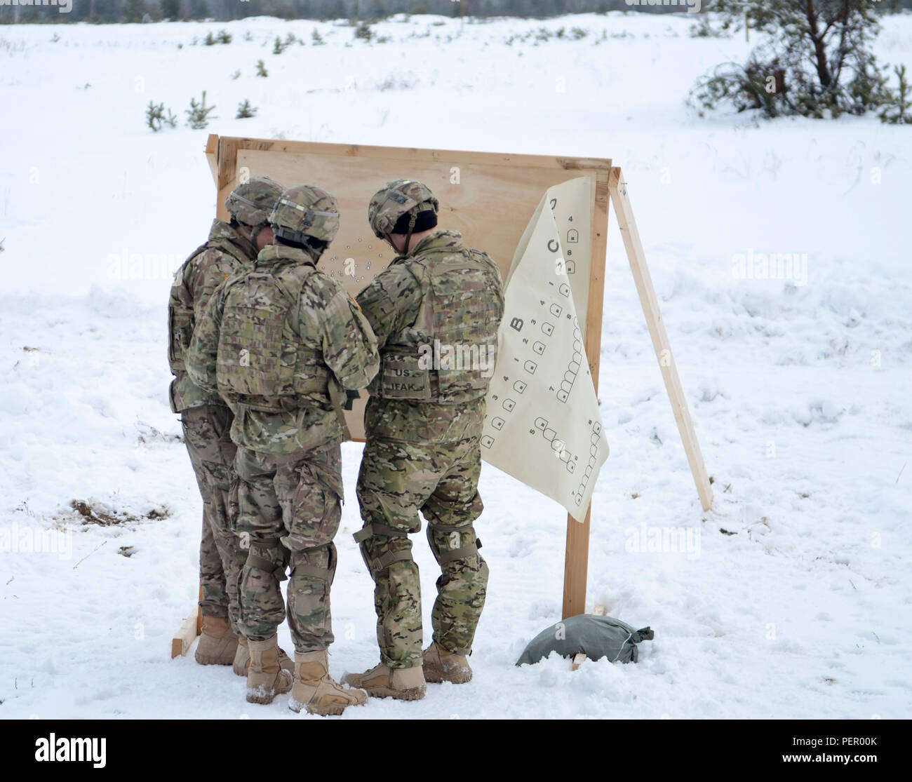 Soldiers of 3rd Squadron, 2nd Cavalry Regiment, stationed at Vilseck, Germany, work together to set up a target for the M240 machine gun range during a training exercise at Adazi Training Area in Latvia, Jan. 25, 2016. (U.S. Army photo by Staff Sgt. Steven Colvin/Released) - Stock Image