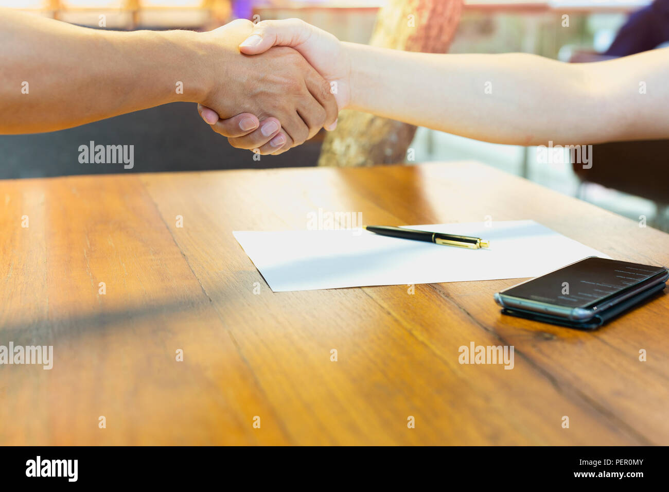 Two man hand shaking hands together with cell phone on wooden table