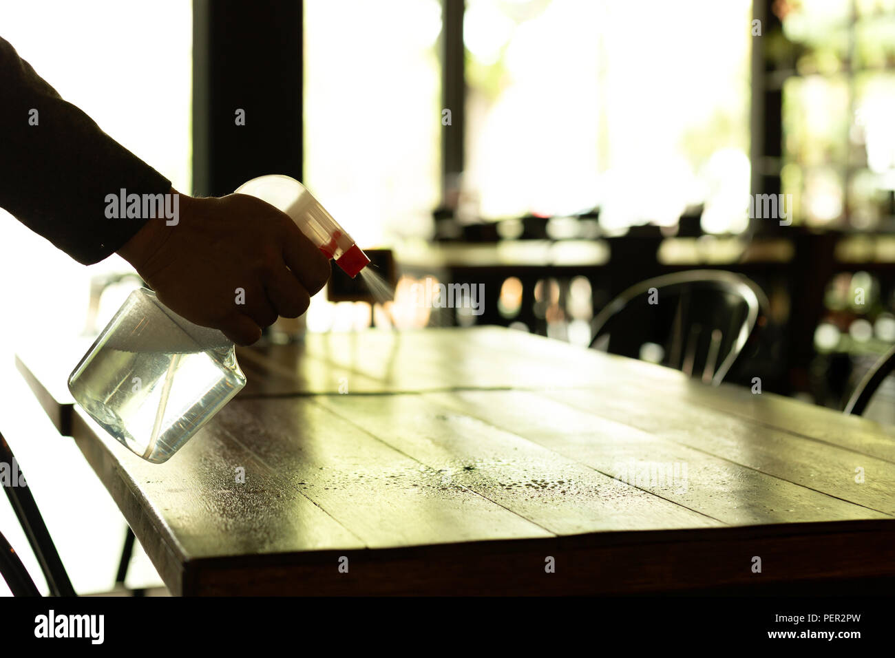 Silhouette waiter cleaning the table with disinfectant spray in a restaurant. - Stock Image