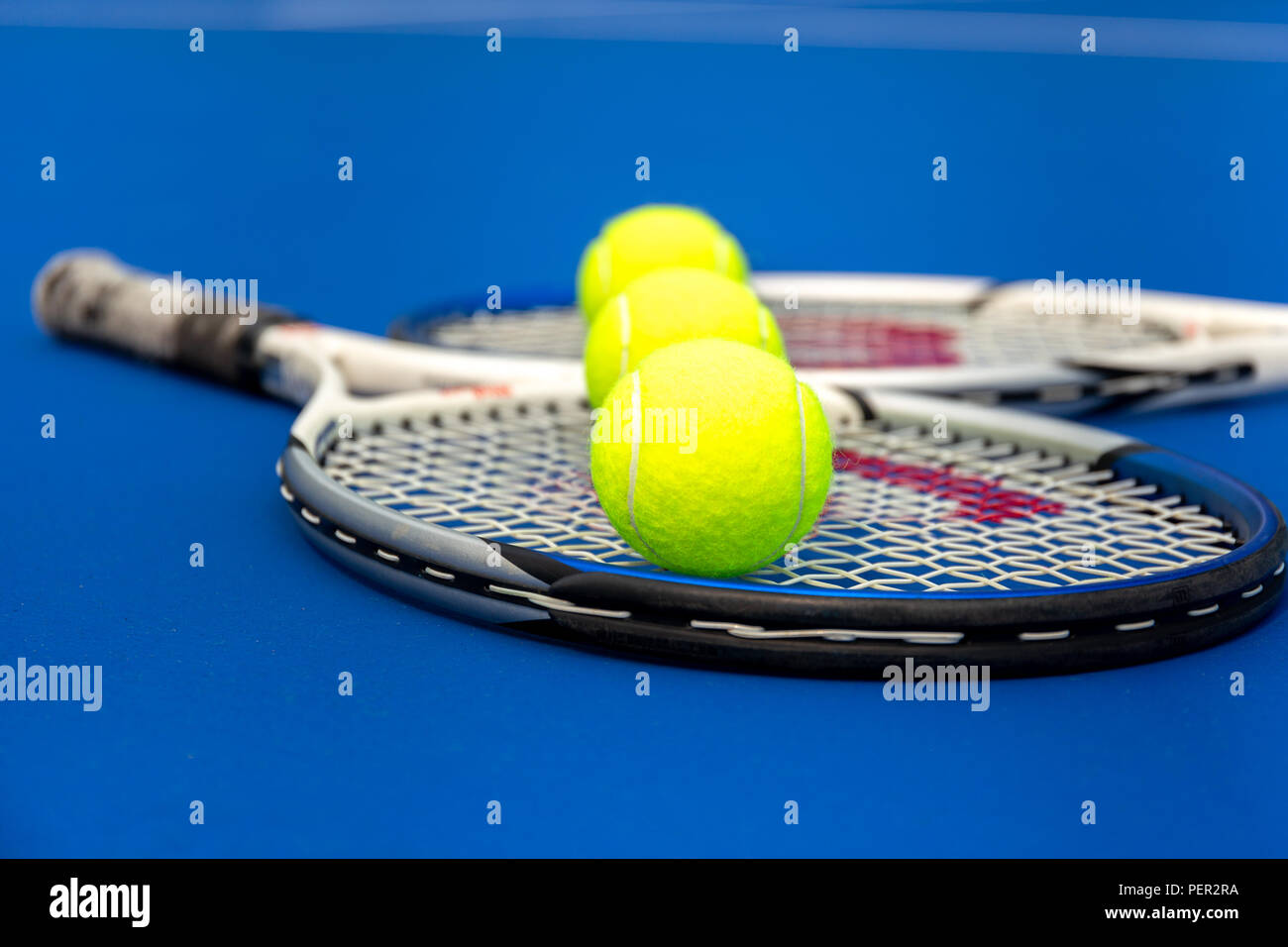 Tennis racket with balls on tennis court outdoor. - Stock Image