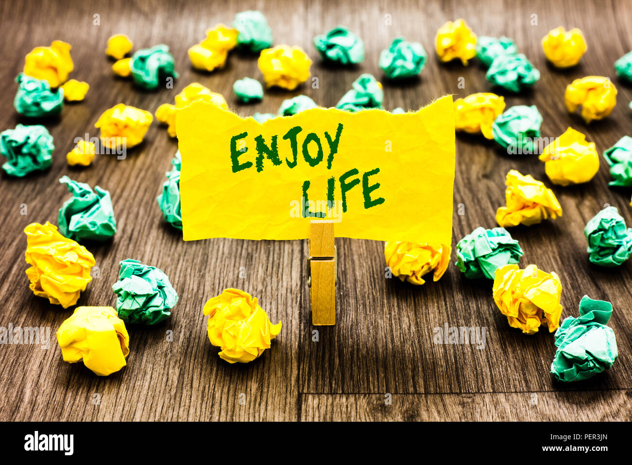 Writing note showing Enjoy Life. Business photo showcasing Any thing, place,food or person, that makes you relax and happy Clothespin holding yellow n - Stock Image