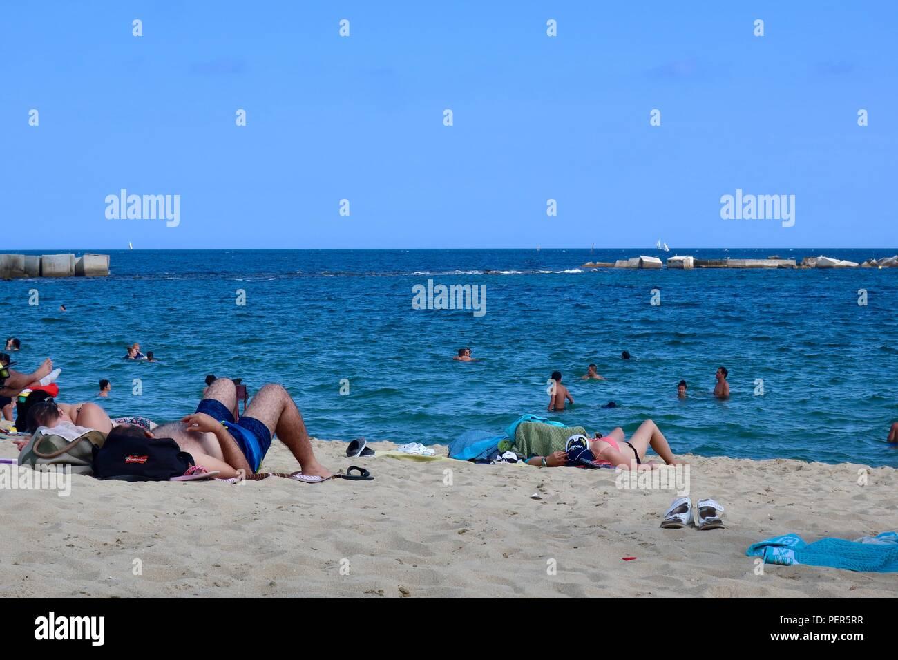 People enjoying platja de la nova icaria / nova icaria beach in Barcelona, Spain. Hot summer afternoon August 2018. - Stock Image