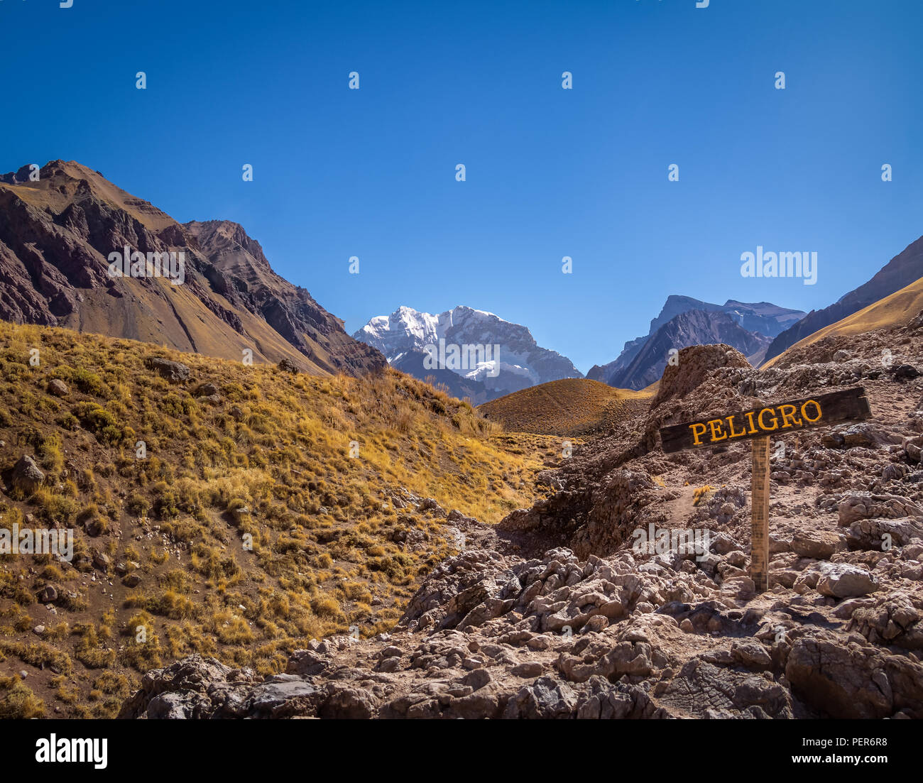 Aconcagua south wall view and danger sign from Aconcagua Provincial Park in Cordillera de Los Andes - Mendoza Province, Argentina - Stock Image