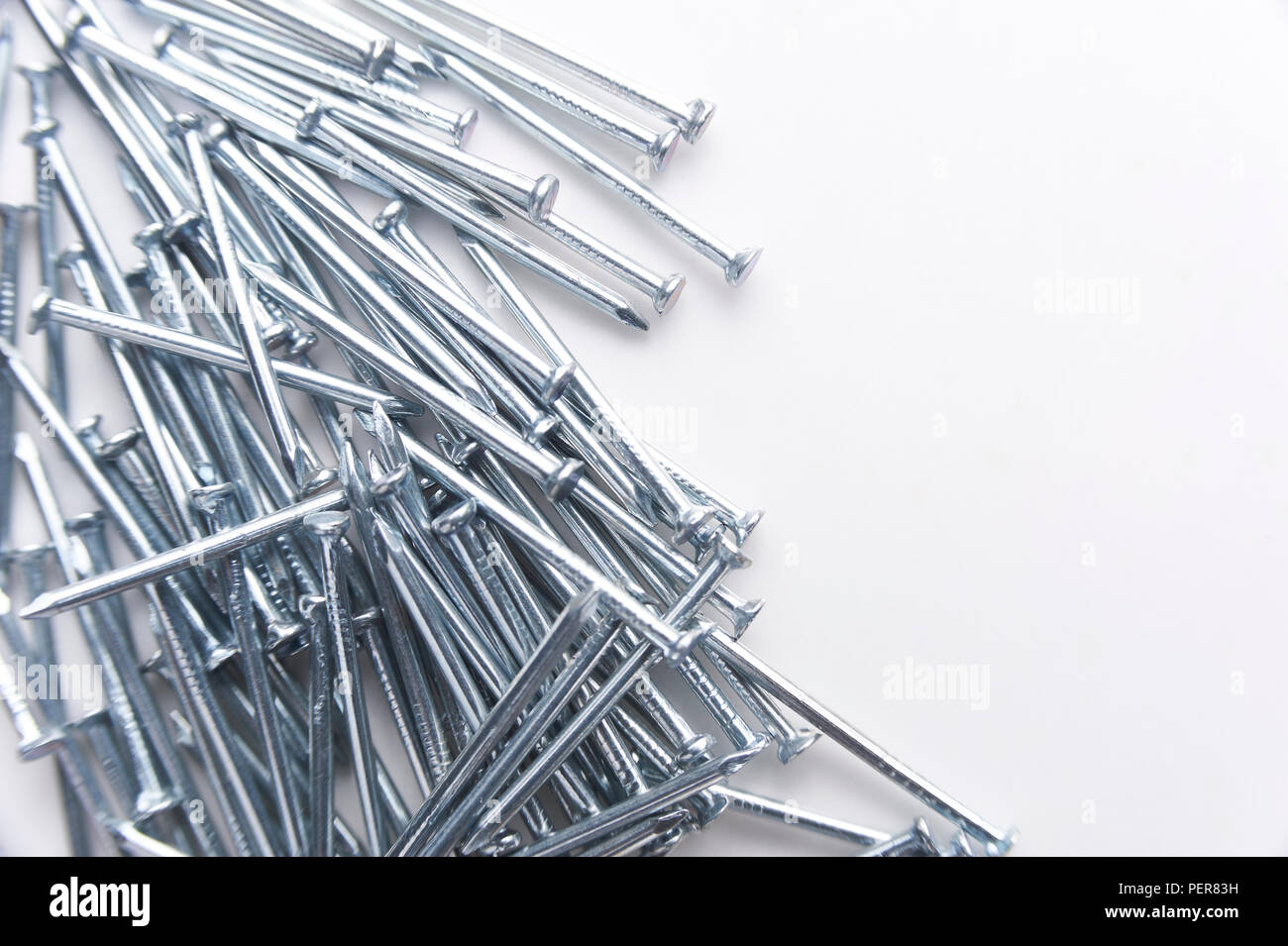 Steel nails on a white background - Stock Image