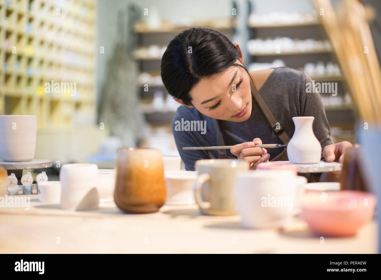 Young potter painting pottery in studio - Stock Image