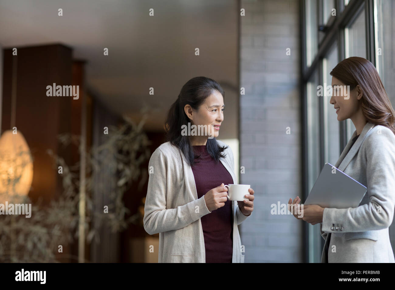 Elegance mature woman talking with young businesswoman - Stock Image