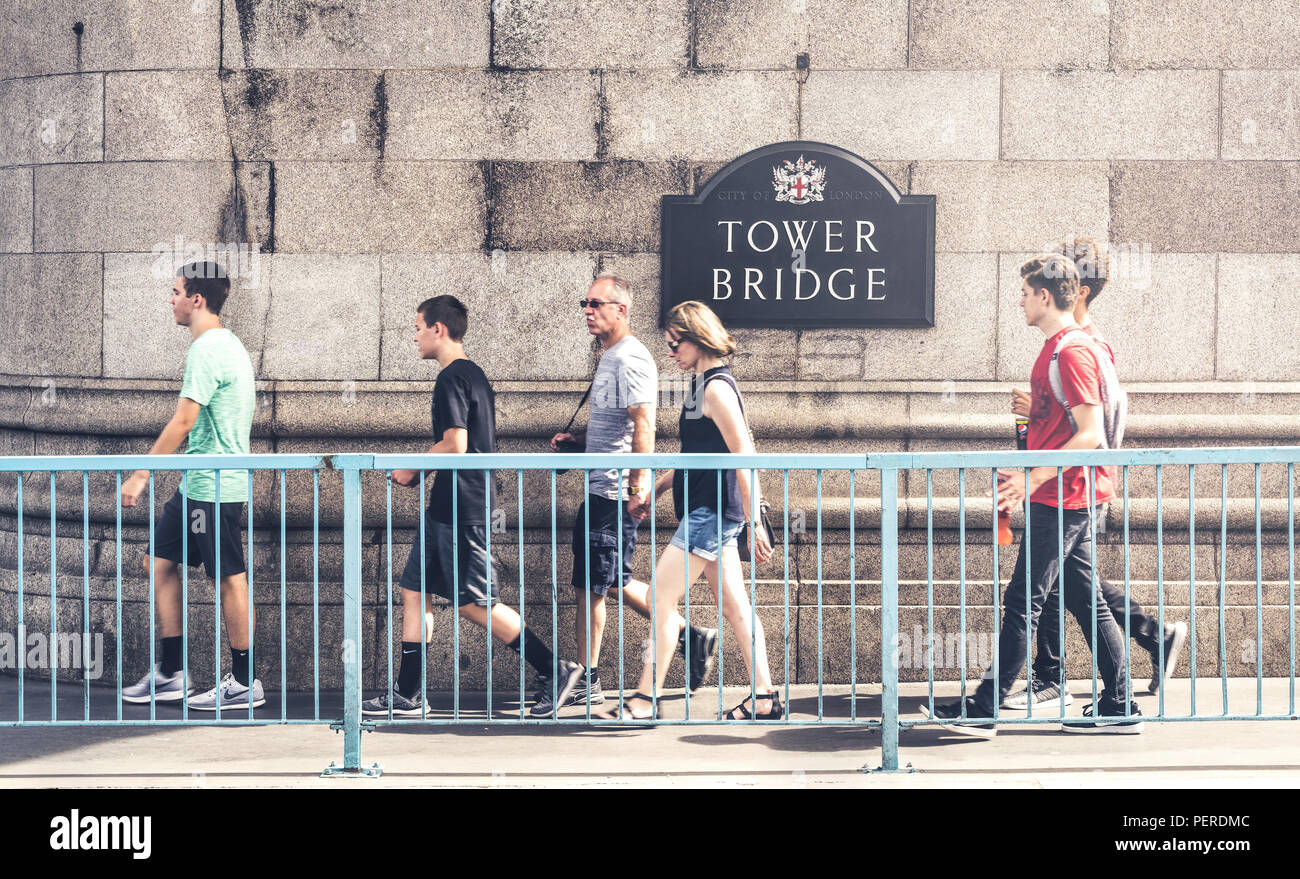 4 August 2018 - London, England. Group of tourists walking on old iconic, symbol of London - Tower Bridge. - Stock Image