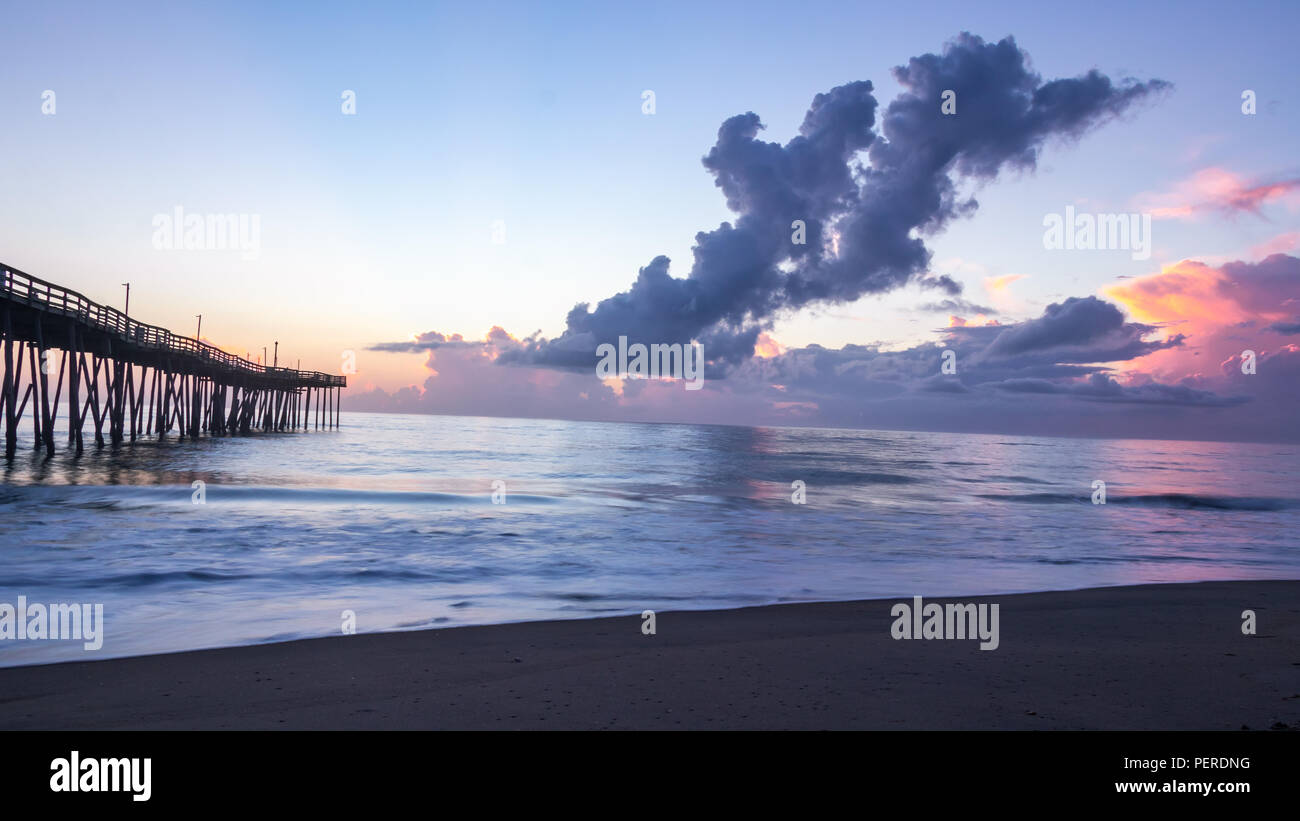 Flat ocean surface reflects the many colors of sunrise. Long exposure photography gives a soft blur with the motion of the sea. Dramatic sky and cloud. - Stock Image