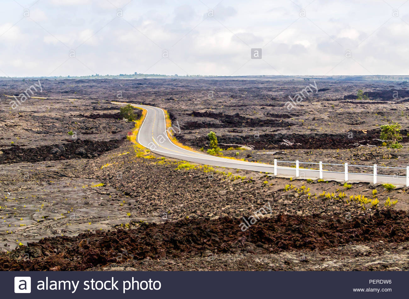 A Lonely Road Curves Through the Lava Fields of Hawaii Volcanoes National Park on the Big Island of Hawaii - Stock Image