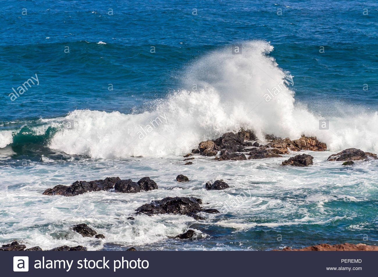 Swells of Surf Crash On To Massive Black Volcanic Rock on the Island of Maui in Hawaii - Stock Image