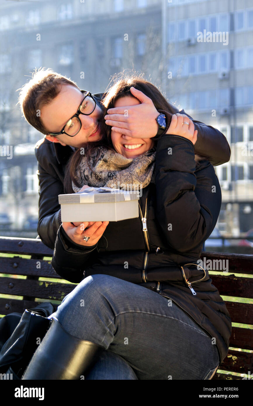 Valentine day. Couple in love. Smiley blindfolded girl receives a present from her boyfriend, guessing the content of present on sunny autumn day. - Stock Image