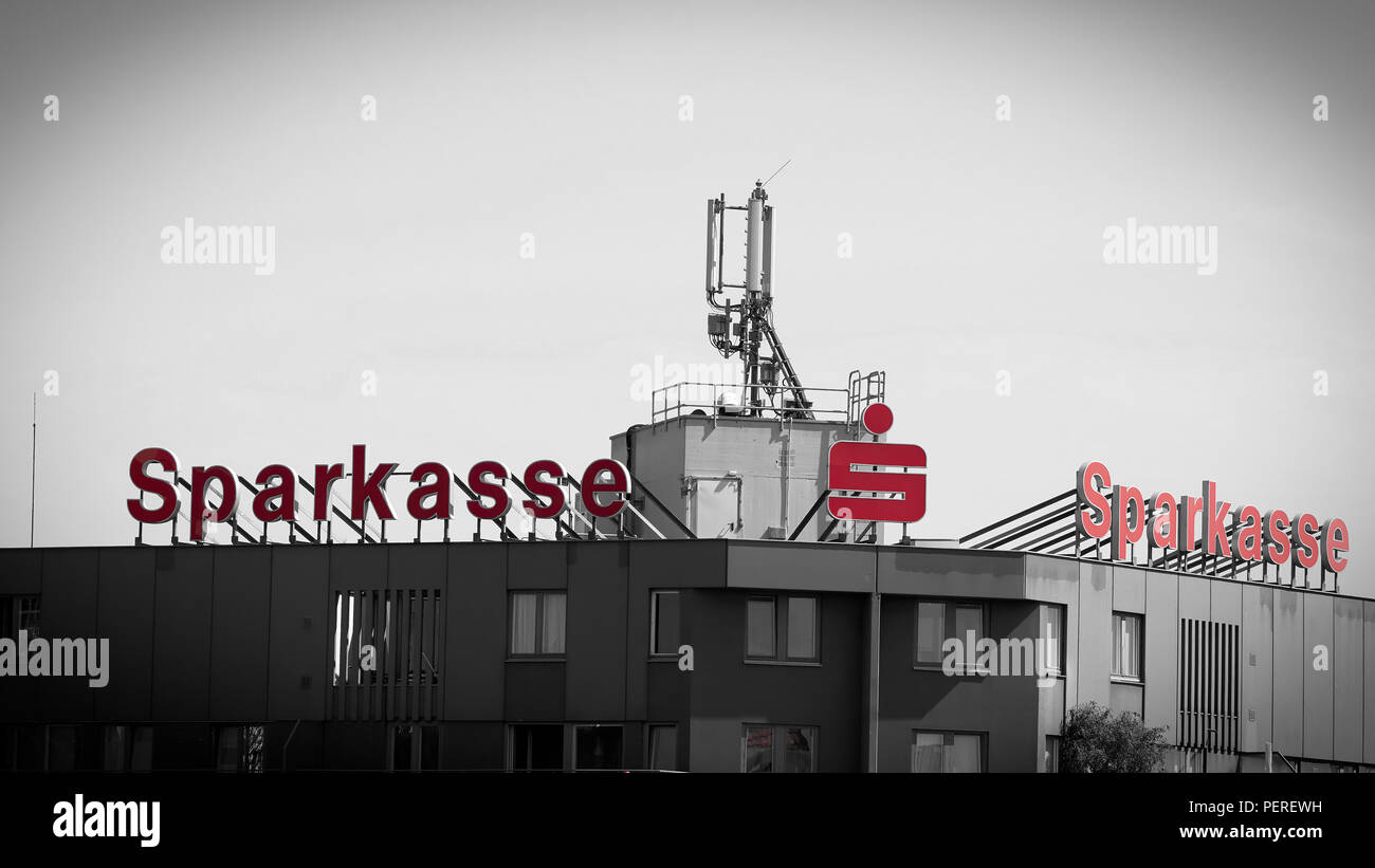 highly visible neon sign on the roof of the bank Sparkasse in downtown Berlin - Stock Image