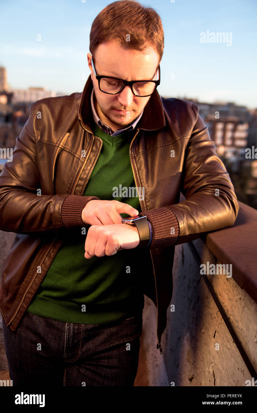 Businessman using his smartwatch touchscreen standing on the roof. Handsome man checking and using his smartwatch. - Stock Image