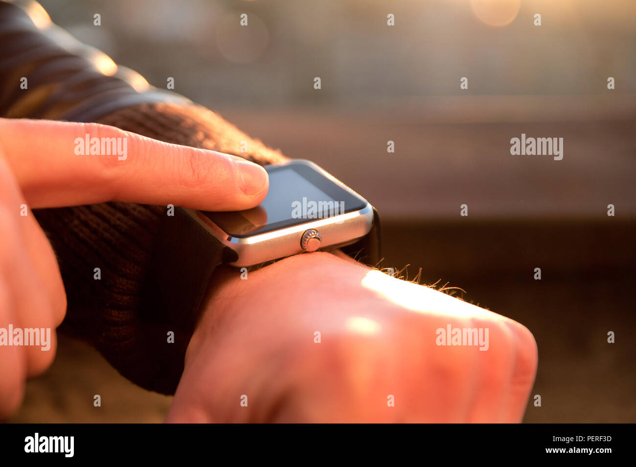 Smartwatch  touchscreen on men's hand and the other hand is working on it. A man using his smartwatch app. Close up hands. - Stock Image