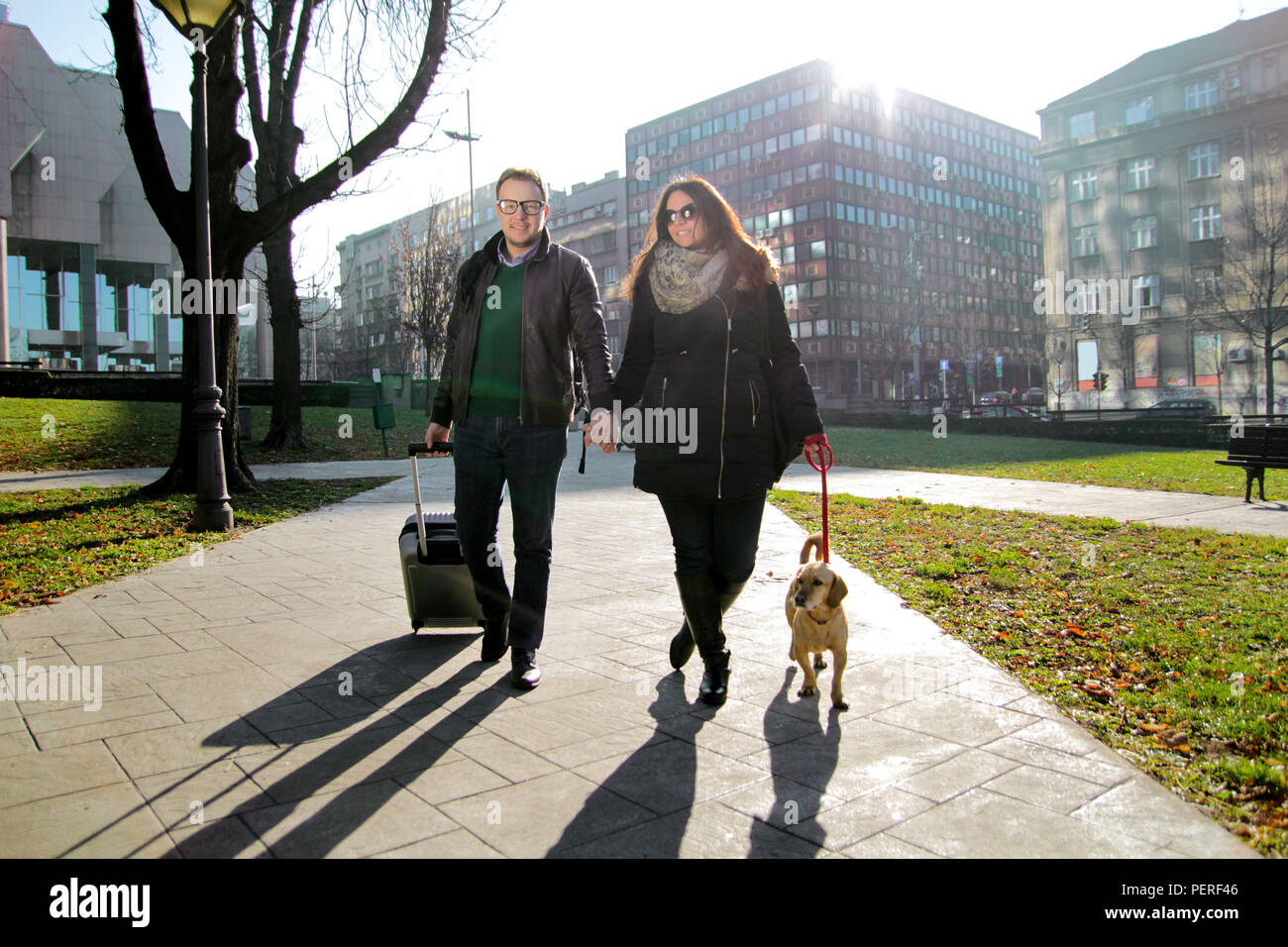Couple with suitcase and dog walking in the park early morning. Happy young couple walking through the park with adorable dog and enjoying. - Stock Image